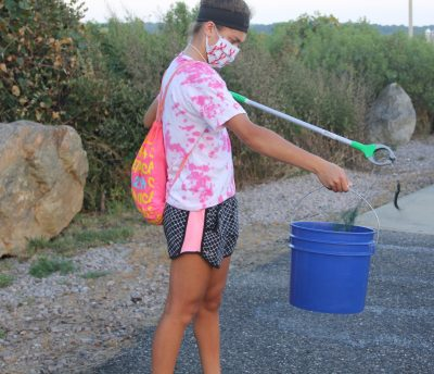 Aria Lupo, a freshman at Princeton University, places a discarded fishing lure with line attached into her bucket.