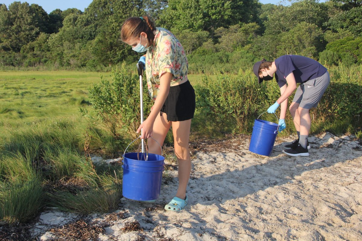 Anna O'Connor, left, a junior at Lyman Memorial High School in Lebanon, and Matthew Fago, a sophomore at RHAM High School in Hebron, search the marsh for trash.