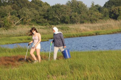Katya Mirsky, left, and Massa Traboulsi, both juniors at Stonington High School, cross the marsh in search of trash.