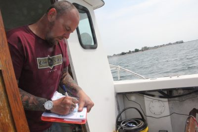 Rick Selen, research vessel engineer aboard the aquaculture bureau's vessel Sea Hawk, record information on the date, time and tidal conditions of each water sample.