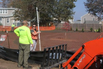 Kristin Walker of the NRCS holds a surveyor's leveling rod as crews from All Habitat Services of Branford plant bayberry, northern white cedar, red oak and other native species at one of the former home sites.