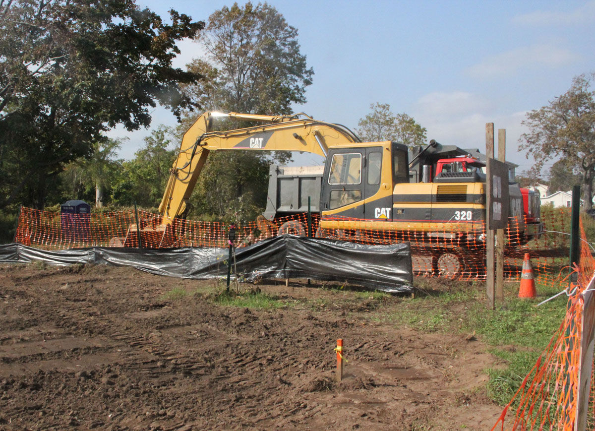 A bulldozer and dump truck are parked beside a former home site being converted into flood plain habitat.