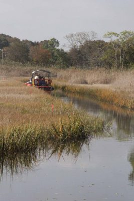 A dredging machine removes silt from Old Field Creek as part of the floodplain restoration project.