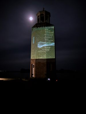 """a """"Reading the Wrack Lines""""Image of a """"Reading the Wrack Lines"""" digital video projection on the UConn Avery Point Lighthouse"""