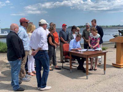 Gov. Lamont signs the Shellfish Restoration Bill on July 23 as legislators and industry members look on.