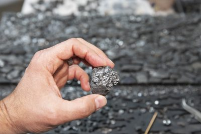 Joseph Smolinski holds one of the pieces of sea coal found on a Long Island Sound beach.