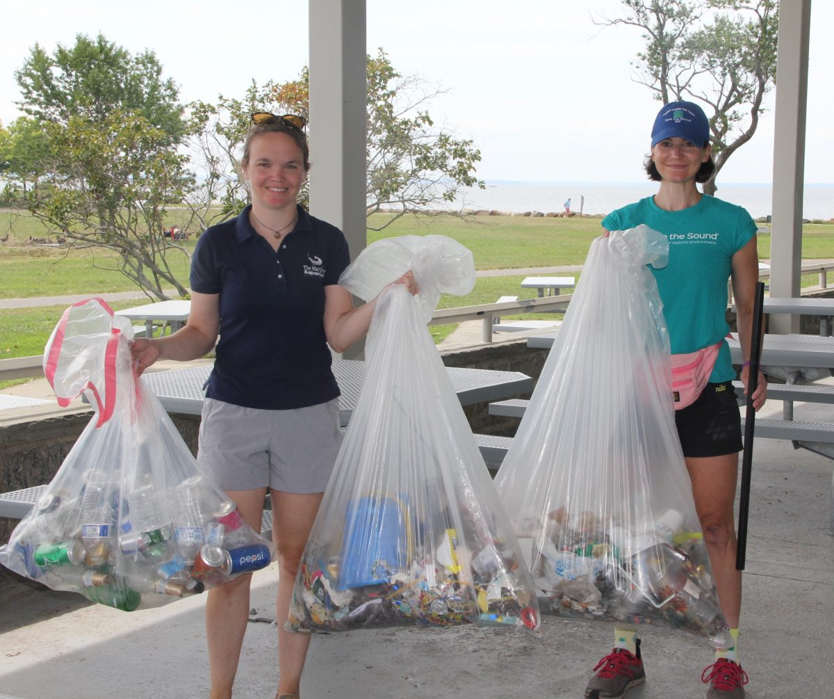 Bridget Cevero of the Maritime Aquarium, left, and Annalisa Paltauf of Save the Sound, hold up the 35.75 pounds of trash collected by volunteers at the cleanup at Sherwood Island State Park.