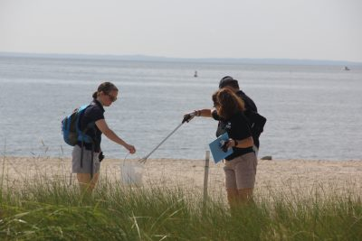 Lisa Jarosik, right, a dive volunteer at the Maritime Aquarium, places trash collected on the beach at Sherwood Island in a bucket held by Bridget Cevero, education manager at the aquarium. Among the items the pair picked up were flip-flops, several tubes of lip balm, large pieces of confetti and a cement trowel.