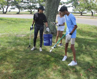 : Palek Mehta, left, and her son Dev and daughter Arya of Westport pick up trash from one of the grassy areas of the park. Dev Mehta is a volunteer at the Maritime Aquarium.