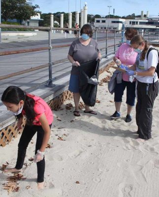 Rebecca Tsai of Groton, left, searches for trash along the edge of the boardwalk as Jeri Buckholt of New London tallies her finds.