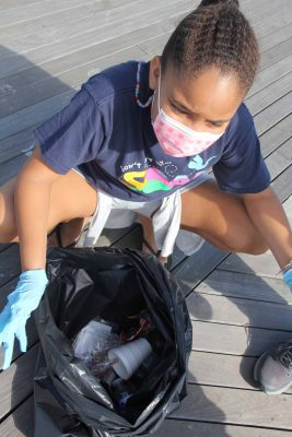 Sveva Brown, a member of New London Girl Scouts, shows some of the trash she collected, including a styrofoam cup, plastic bottles and food wrappers.